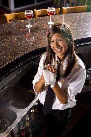 manos limpias: Camarero mujer hispana secarse las manos detr�s de la barra de Foto de archivo