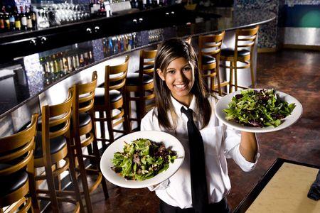 Hispanic waitress in restaurant serving salad plates 스톡 콘텐츠