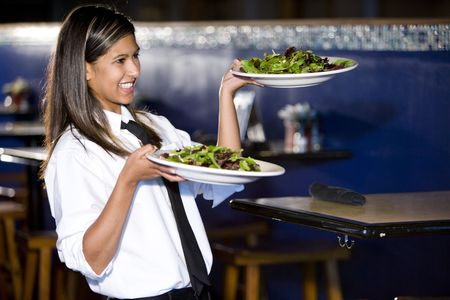 Cheerful Hispanic waitress serving salad plates in restaurant