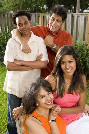 Interracial African American and Hispanic family relaxing in back yard photo