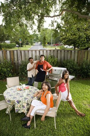 Interracial African American and Hispanic family having back yard barbecue photo