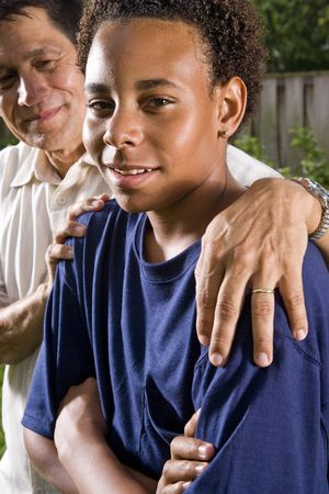 Interracial family, portrait of African teenage boy with proud Hispanic father photo