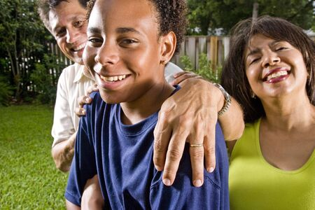 cropped out: Interracial family, portrait of African teenage boy with proud parents