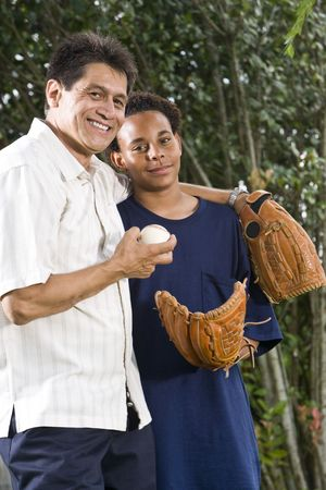 cropped out: African American teenage boy with proud Hispanic father Stock Photo