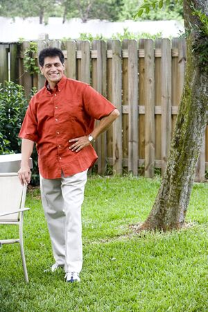 back yard: Portrait of mature Hispanic man standing in back yard