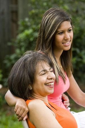 Hispanic teenage girl with African American mother sitting together photo