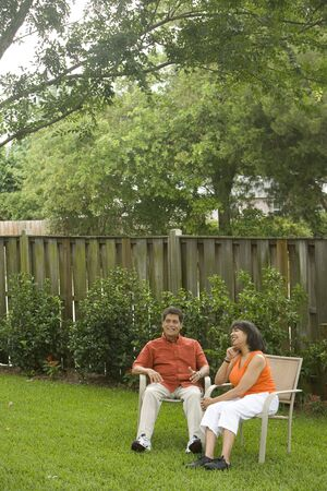 back yard: Hispanic husband and African American wife relaxing in back yard Stock Photo