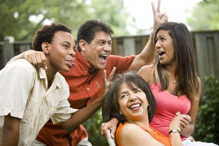 parent and teenager: Interracial African American and Hispanic family making silly gestures posing for photograph