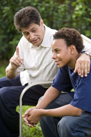 back yard: Interracial Hispanic father and African American teenage son together in back yard Stock Photo