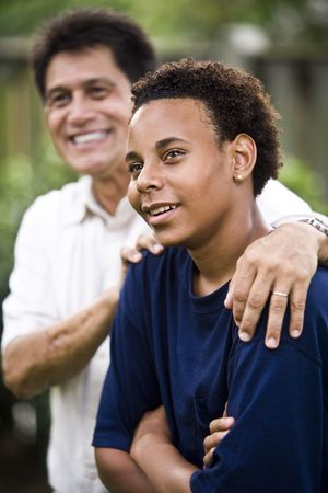 Hispanic father and African American teenage son together in back yard photo