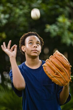 African American teenage boy tossing a baseball up in the air