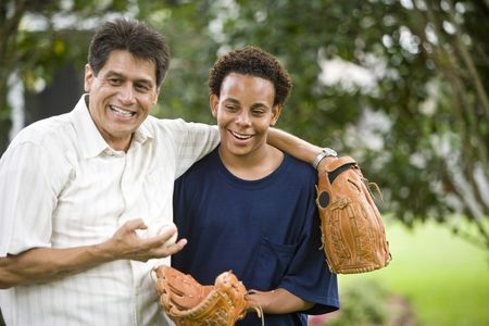Interracial Hispanic father and African American teenage son with baseball gloves