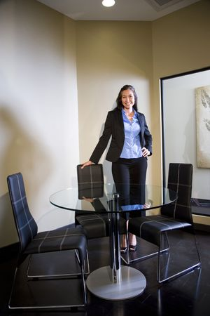 round chairs: Portrait of young confident office worker standing next to round glass table Stock Photo