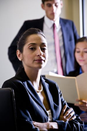 Serious Hispanic businesswoman with colleagues working in background photo