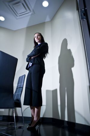 Serious young businesswoman standing in an office photo