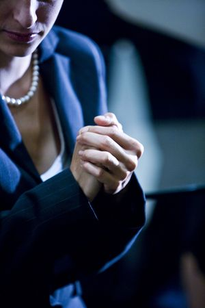 Close-up of hands of well-dressed woman clasped together