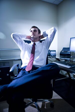 office desk: Young confident office worker relaxing in office