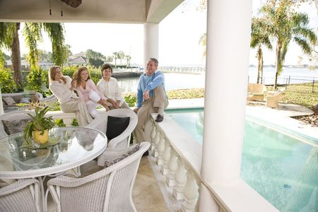 wealthy: Portrait of family on vacation relaxing on terrace together Stock Photo