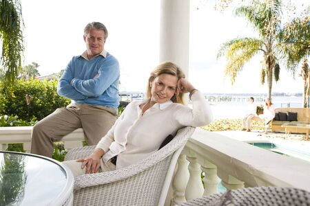 affluent: Portrait of mature couple relaxing on waterfront terrace Stock Photo