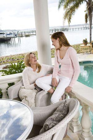 Mère et adolescente parler sur la terrasse du secteur riverain Banque d'images - 6329069