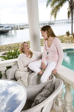 Mother and teenage daughter talking on waterfront terrace photo