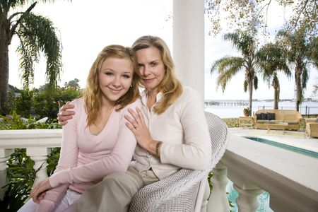 affluent: Portrait of mother and daughter on waterfront terrace Stock Photo