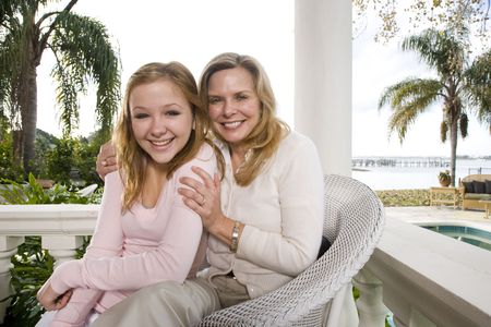 Portrait of mother and daughter on waterfront terrace 版權商用圖片