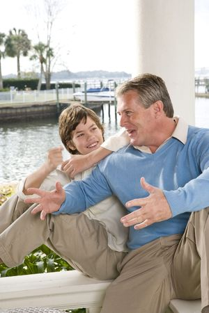 Father and son talking on waterfront terrace