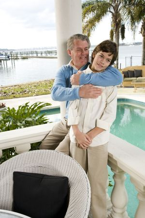 Portrait of affectionate father and son on waterfront terrace photo