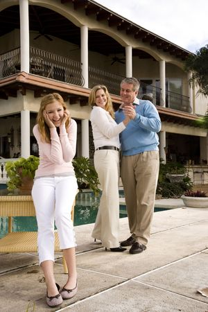 Mature couple dancing in front of amused teen daughter photo
