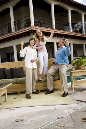 Father with his children playing air guitar on patio photo