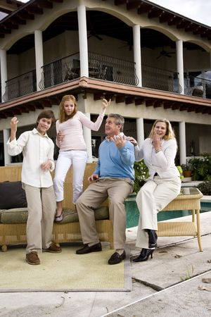 air guitar: Portrait of carefree family of four playing air guitar on patio