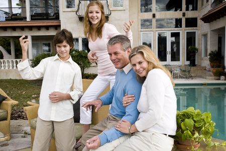 air guitar: Portrait of carefree family, kids playing air guitar on patio Stock Photo