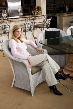 Portrait of smiling mature woman sitting in white wicker chair at dining room table