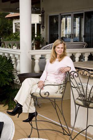 barstools: Portrait of smiling mature woman sitting on wrought iron barstool