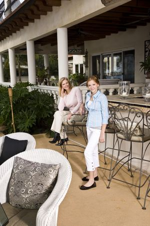barstools: Portrait of mother and daughter relaxing on patio
