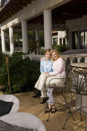 barstools: Portrait of affectionate mother and daughter relaxing on patio
