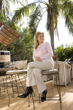 barstool: Mature woman on tropical vacation at a resort sitting outdoors Stock Photo