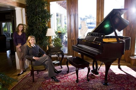Portrait of mature woman and teen girl next to grand piano photo