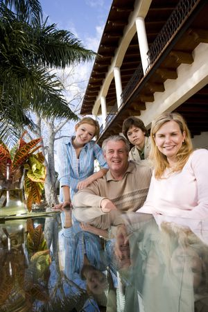Portrait of family sitting at outdoor glass table photo