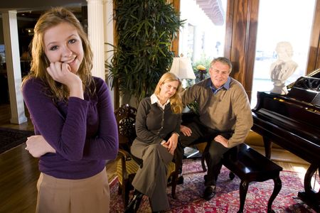 oriental rug: Portrait of smiling teenage girl, parents sitting next to grand piano in background Stock Photo