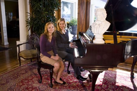 piano lesson: Portrait of mother and teen daughter sitting at grand piano
