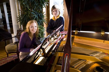 younger: Teenage girl playing piano while younger brother stands beside