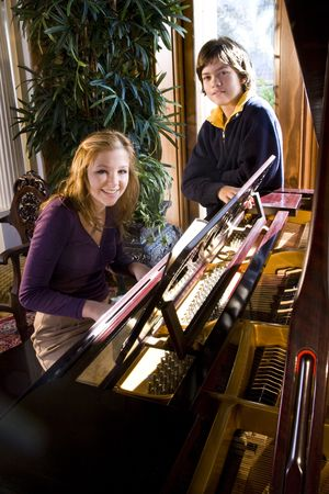 Teenage girl playing piano while younger brother stands beside photo