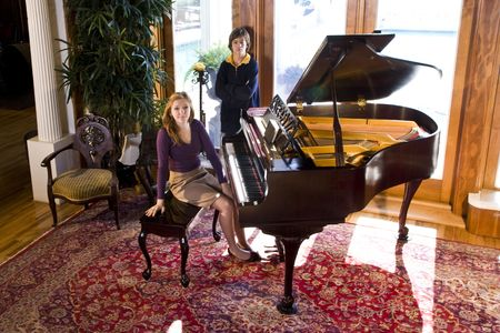 oriental rug: Portrait of teenage girl and younger brother next to grand piano