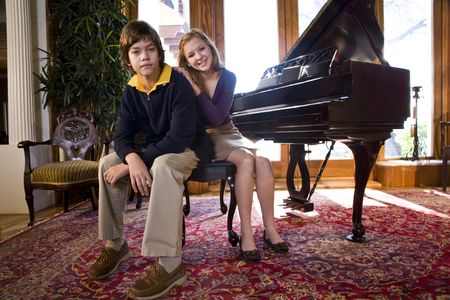 Portrait of teenage girl and younger brother next to grand piano Stock Photo - 6329059