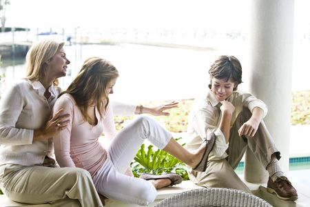 Family sitting on terrace together, teenager girl kicking younger brother Stock Photo - 6328937