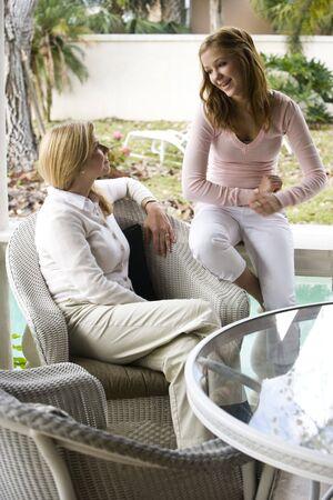 dos personas conversando: La madre y la hija adolescente chateando juntos en patio Foto de archivo