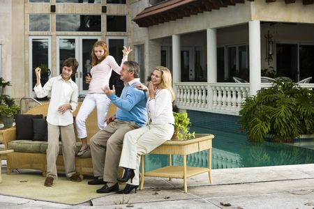 Family relaxing on patio together playing air guitar photo
