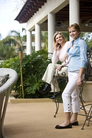 Portrait of mother and daughter relaxing on patio photo